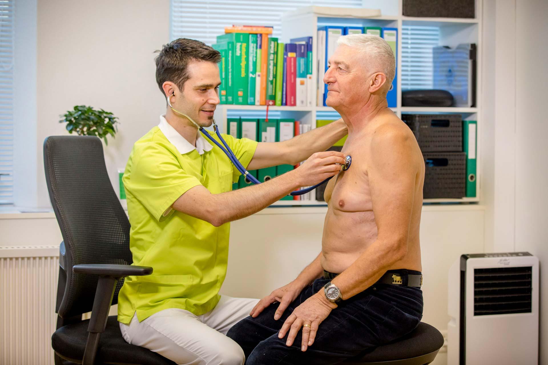 Naturheilpraktiker untersucht älteren Mann